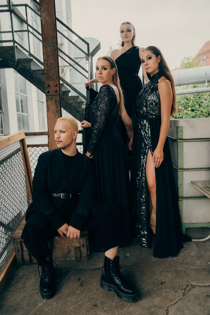 Modeaufnahme von vier Models an einer Treppe in schwarzen Outfits