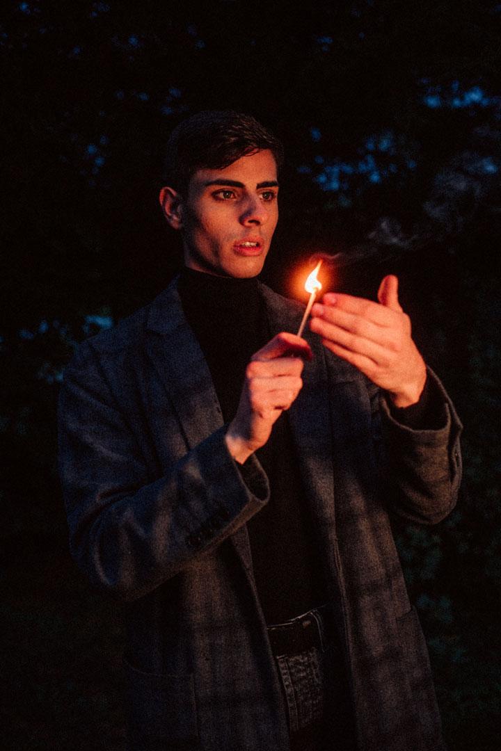 Männliches Model im schwarzen Mantel mit Streichholz in der Hand