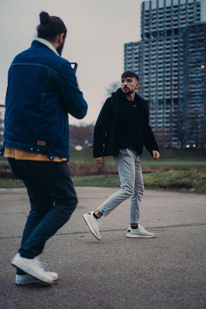 Kameramann läuft im Freien hinter männlichen Model her