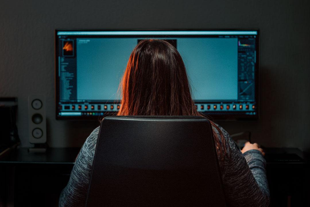Person sitzt vor Bildschirm und arbeitet